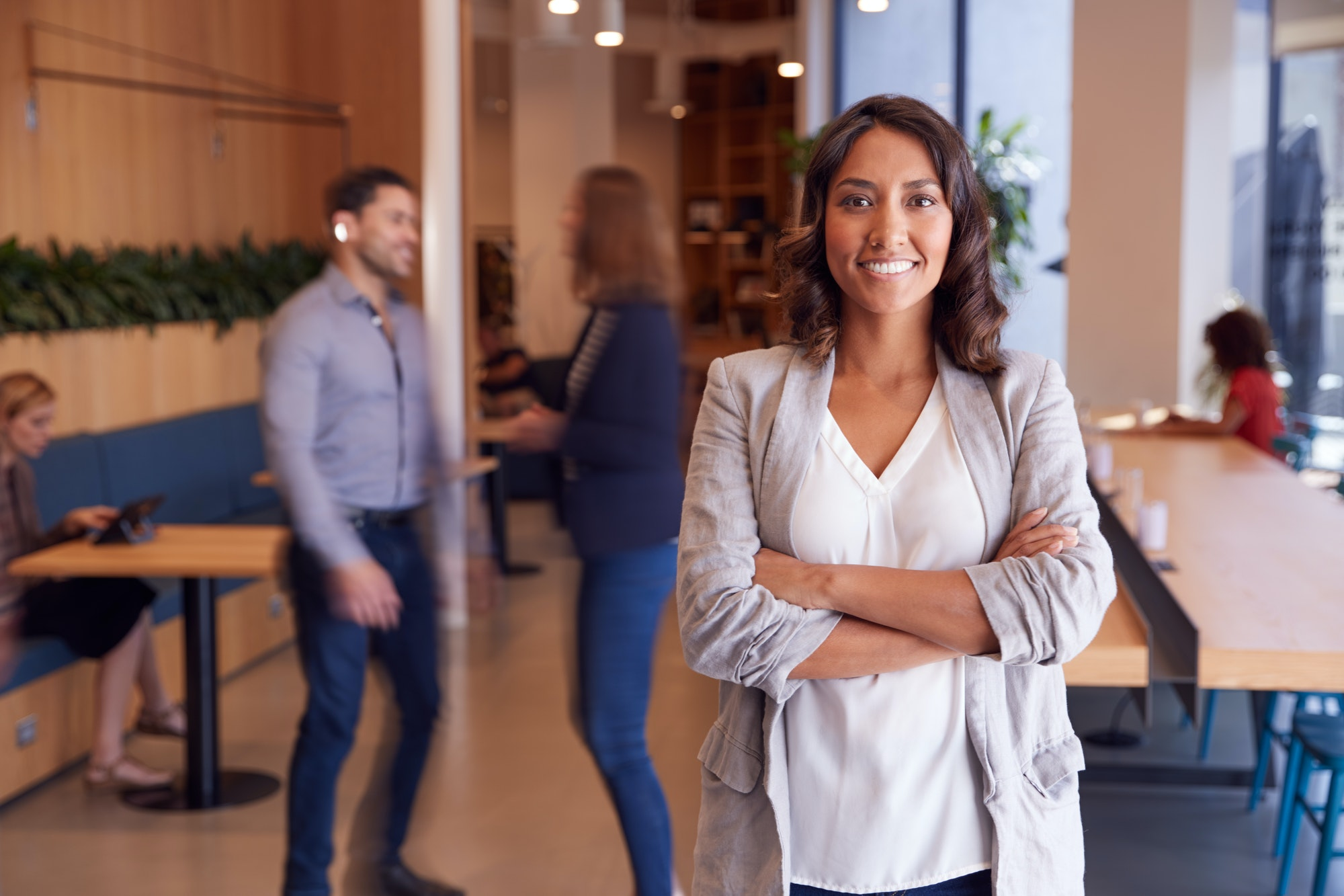 Portrait Of Businesswoman Standing In Busy Modern Open Plan Office With Colleagues In Background